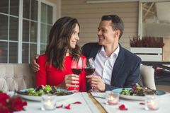 Young couple having romantic dinner in the restaurant sitting together looking on each other. Young men and women having romantic dinner in the restaurant Stock Photos