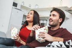 Young couple having romantic evening at home watching comedy movie. Young men and women having romantic evening indoors eating noodles watching comedy movie Royalty Free Stock Images
