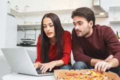 Young couple having romantic evening at home working on laptop. Young men and women having romantic evening indoors eating pizza working on laptop browsing Stock Photos