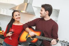 Young couple having romantic evening at home in the kitchen man playing guitar. Young men and women having romantic evening indoors in the kitchen boyfriend Royalty Free Stock Photos