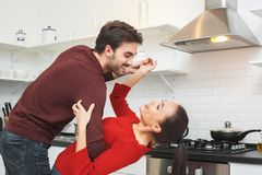 Young couple having romantic evening at home in the kitchen dancing. Young men and women having romantic evening indoors in the kitchen dancing holding hands royalty free stock photography