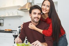 Young couple having romantic evening at home in the kitchen hugging looking camera. Young men and women having romantic evening indoors in the kitchen wife Royalty Free Stock Photography