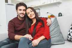 Young couple having romantic evening at home hugging looking camera Royalty Free Stock Photos