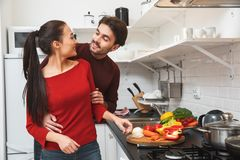 Young couple having romantic evening at home in the kitchen cooking together hugging. Young men and women having romantic evening in the kitchen cooking dinner Stock Photo