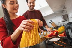 Young couple having romantic evening at home in the kitchen cooking meal together close-up stock photography