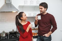 Young couple having romantic evening at home in the kitchen drinking hot coffee. Young men and women having romantic evening in the kitchen drinking hot coffee Royalty Free Stock Image