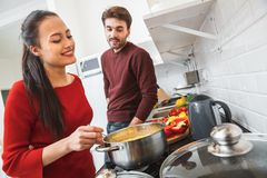 Young couple having romantic evening at home in the kitchen cooking pasta. Young men and women having romantic evening in the kitchen girlfriend cooking pasta Royalty Free Stock Photography