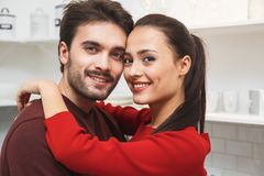 Young couple having romantic evening at home in the kitchen looking camera close-up. Young men and women having romantic evening in the kitchen hugging looking Stock Images