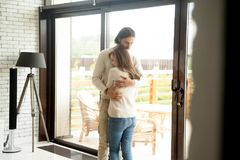 Young man and woman hugging standing at home, couple reconcilia. Young men and women hugging standing at home interior, tender husband embracing wife gently stock photos
