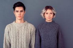 Young man and woman studio shoot on grey wall serious royalty free stock image