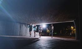 Young men and women jogging together at night Royalty Free Stock Images