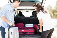 Couple leaving for vacation loading luggage into car. Young men and women loading their bags into car trunk before going for road trip Royalty Free Stock Image
