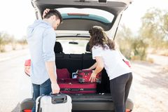 Couple loading suitcases into car. Young men and women loading their luggage in hatchback car boot and getting ready for their road trip stock photography
