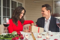 Young couple having romantic dinner in the restaurant looking at present. Young men and women looking at present shy having romantic dinner in the restaurant Royalty Free Stock Image