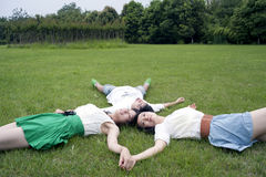 Young men and women lying on the grass Stock Image