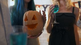Young men and women partying with Halloween pumpkin, drinking alcohol together