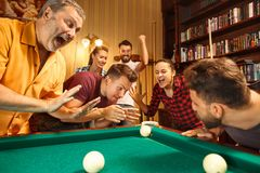 Young men and women playing billiards at office after work. Young smiling men and women playing billiards at office or home after work. Business colleagues Royalty Free Stock Image