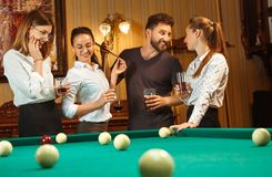 Young men and women playing billiards at office after work. Young smiling men and women playing billiards at office or home after work. Business colleagues Royalty Free Stock Photography
