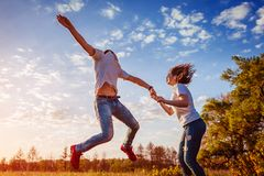 Young man and woman running and jumping. Couple having fun in spring field at sunset. Guys enjoying life. royalty free stock photography