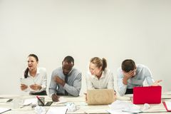Young men and women sitting at office and working on laptops. Emotions concept stock image