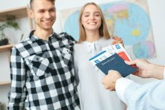 Young couple in a tour agency communication with a travel agent travelling concept giving documents. Young men and women smiling happy in a tour agency with a Stock Images