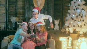 Young men and women taking self photograph at Christmas party. Cheerful friends making selfie. Slow motion. stock video