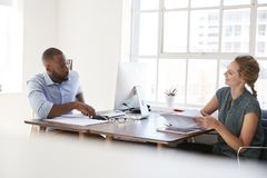 Young man and woman talking across their desks in an office Stock Images