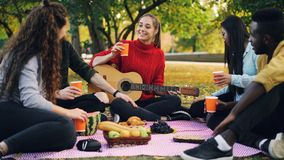Young men and women are toasting and clinking glasses on picnic in park with guitar on warm autumn day. Friendship stock photography
