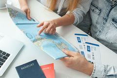 Young couple in a tour agency travelling concept choosing destination close-up. Young men and women in a tour agency choosing destination on a map close-up Royalty Free Stock Images