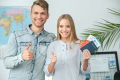 Young couple in a tour agency travelling concept holding documents thumbs up royalty free stock images