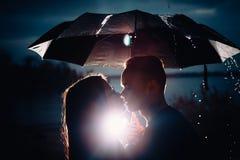 Young man and woman under an umbrella and rain royalty free stock photos