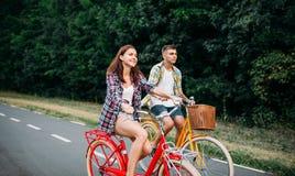 Young man and woman walking on retro bikes Stock Photos