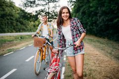Young man and woman walking on retro bikes Stock Images