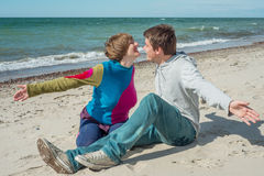 Young men and women want to cuddle on the beach Stock Images