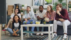 Young men and women watching TV laughing eating popcorn in apartment together