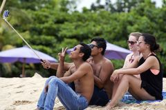 Young men and women wearing sunglasses take selfie with using a selfie stick on the beach. Young men and women wearing sunglasses, swimsuits  and blue jeans take Royalty Free Stock Photos