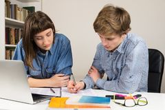 Female and male students co-working on a school or work assignment. Young men and women work together at home office desk Royalty Free Stock Image