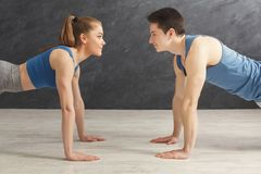 Couple making plank or push ups exercise indoors. Young men and women workout in fitness club. Fitness couple making plank or push ups exercise face to face stock photos