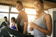 Young man and women workout in gym. royalty free stock photography