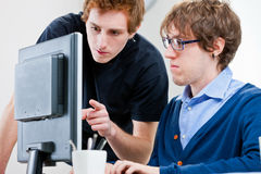 Young men working together in an office Stock Image