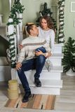 Young man and a young girl are sitting on the steps of a white staircase in a house in the eve of New Year holidays. Girl and guy. Young men and a young girl are royalty free stock images