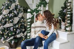 Young man and a young girl are sitting on the steps of a white staircase in a house in the eve of New Year holidays and are kiss. Young men and a young girl are royalty free stock photography