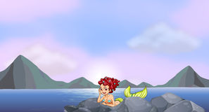 A young mermaid near the rocks at the seaside Royalty Free Stock Image