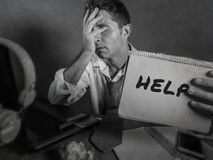 Young messy and depressed business man showing notepad asking for help desperate and sad at office laptop computer desk looking ov. Erwhelmed and worried in stock images
