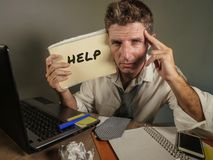 Young messy and depressed business man showing notepad asking for help desperate and sad at office laptop computer desk looking ov. Erwhelmed and worried in royalty free stock image