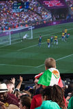 Young Mexican Fan watching the Olympic Final. A Young Mexican Fan watches the Olympic 2012 Football Final amongst the crowds of thousands of people watching the Stock Image