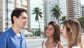 Young mexican guy talking with two girlfriends in the city royalty free stock images