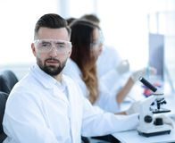 Microbiologist and his colleagues are sitting in a modern laboratory. Young, microbiologist and his colleagues are sitting in a modern laboratory Stock Images