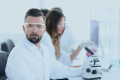 Microbiologist and his colleagues are sitting in a modern laboratory. Young, microbiologist and his colleagues are sitting in a modern laboratory Royalty Free Stock Photos