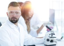 Microbiologist and his colleagues are sitting in a modern laboratory. Young, microbiologist and his colleagues are sitting in a modern laboratory Royalty Free Stock Photography